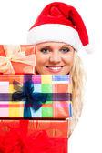 Attraktive frau in nikolausmütze mit weihnachtsgeschenke — Stockfoto