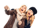 Shocked women in winter clothes pointing — Stock Photo