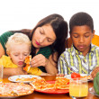 Mother with kids eating pizza — Stock Photo