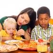 Mother with kids eating pizza - Stock Photo