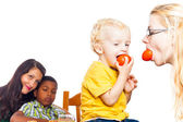 Funny woman and child eating tomato — Stock Photo