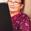 Happy elderly woman with laptop — Stock Photo
