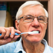 Stock Photo: Senior mbrushing his teeth