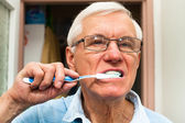 Senior man brushing his teeth — Stock fotografie