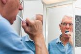 Alter mann im spiegel seiner zähne putzen — Stockfoto