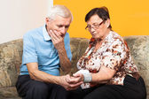 Worried seniors measuring blood pressure — Stock Photo