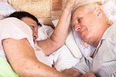 Dva senioři odpočívat v posteli — Stock fotografie
