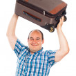 Happy traveler lifting up his luggage — Stock Photo
