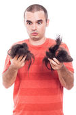 Shocked bald man holding his shaved hair — Stock Photo