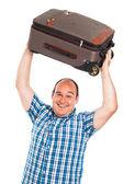 Laughing traveler lifting up his luggage — Stock Photo