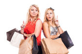 Pensive girls shopping and pointing up — Stock Photo