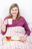 Happy woman enjoying breakfast in bed — Stock fotografie