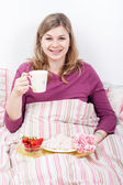 快乐享受早餐躺在床上的女人 — 图库照片