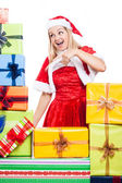 Christmas woman pointing at presents — Stock Photo