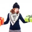 Indecisive woman holding gifts — Stock Photo
