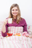 Happy woman with cup of coffee and breakfast — Stock Photo