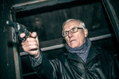 Dangerous senior with a gun — Stock Photo