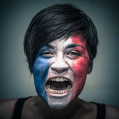 Angry woman with flag of France painted on face — Stock Photo