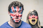 Scary couple with British and German flag on face — Stock Photo