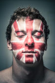 Man with British flag on face and closed eyes — Stock Photo