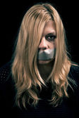 Kidnapped woman hostage with tape over her mouth — Stock Photo