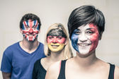 Happy people with painted flags on faces — Stock Photo