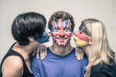 Happy friends with painted flags on faces kissing — Stock Photo