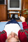 Elderly man with remote control watching TV — Stock Photo