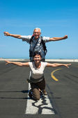 Happy couple imitating airplane at the airport — Stock Photo