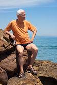 Senior tourist man on the rocky beach — Stock Photo