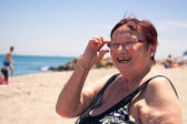 Happy senior woman on the beach — Stock Photo