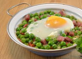 Peas cooked with ham and egg — Stock Photo