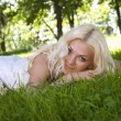 Smiling Blonde Bride Lying on Grass — Stock Photo