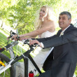 Newlywed couple riding bicycle — 图库照片