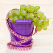 Ripe green grapes in pail on wooden table — Stock Photo #48167493