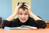 Boy student grabbed his head due to the difficult lessons — Stock Photo