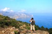 Photographer and traveler photographs beautiful seascape — Stock Photo