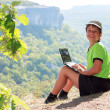 Smiling boy in green t-shirt with a netbook on top of the mounta — Stock Photo
