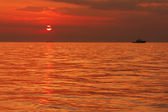 Seascape with a boat on the background of sunset — Stock Photo