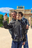 Man and teen in Paris take a selfie in front of The Arc de Triom — Stock Photo