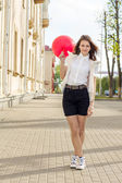 Beautiful fashion girl with red balloon on the street  — Stock Photo
