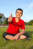 Laughing teenage summer in the grass thumbs up — Stock Photo