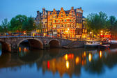 Night city view of Amsterdam canal and bridge — Stock Photo
