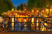 Night  illumination of Amsterdam canal and bridge — Stock Photo