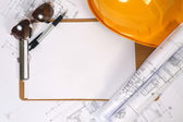 Yellow hard hat and blueprints — Stock Photo