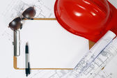 Red hard hat and blueprints — Stock Photo