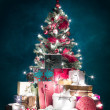 Brightly lit christmas tree with presents - Stock Photo
