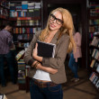 Young attractive blonde girl in bookstore — Stock Photo #19986419