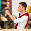 Handsome bartender preparing a drink — Stock Photo