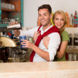 Happy couple prepaing a drink - Stock Photo